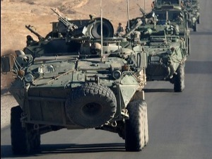 3 tanks drive down a street in the desert