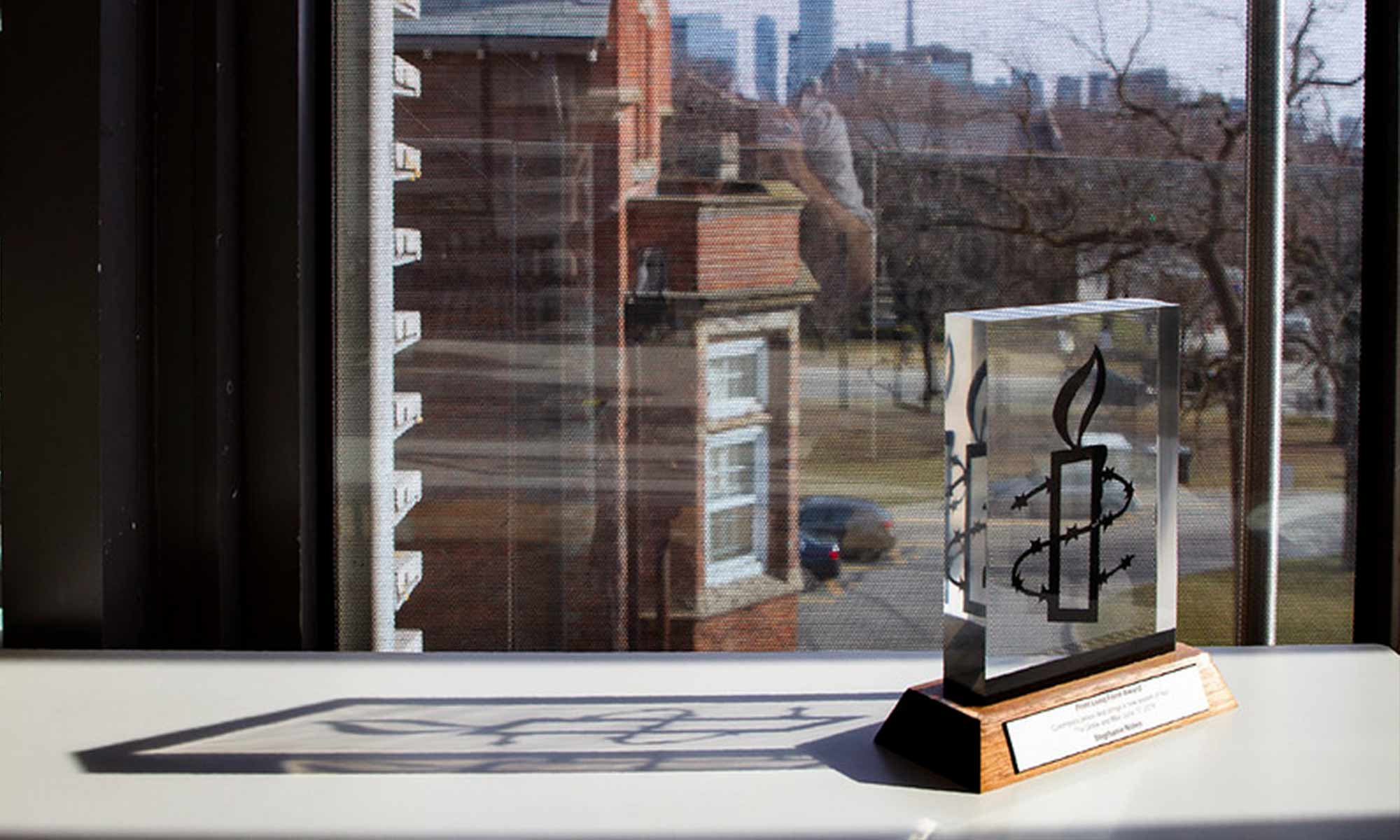 A square glass trophy with a wooden base sitting on a table in front of a window.